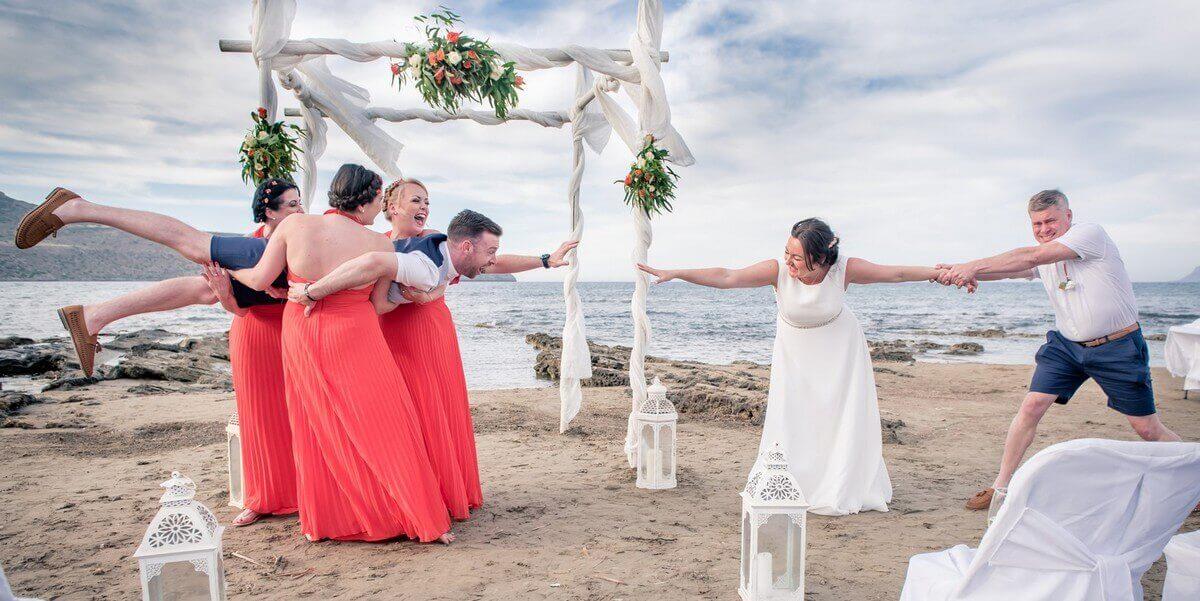 Bridesmaids lift groom at Crete beach wedding