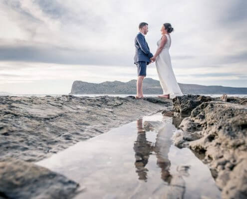 Bride and groom hold hands with reflection in rock pool at Crete beach wedding