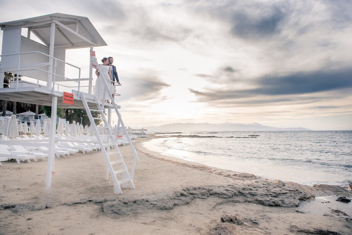 Bride and groom on life guard tower at Crete beach wedding
