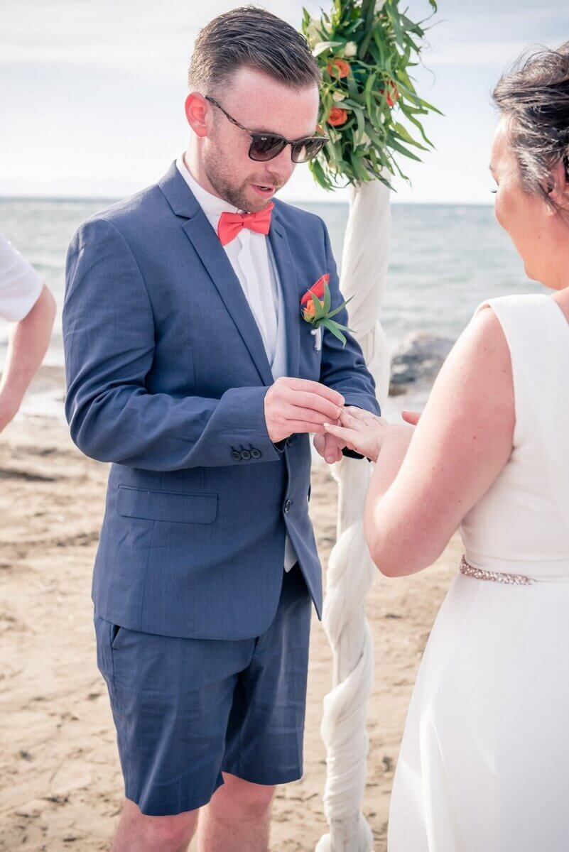 Groom putting ring on brides finger at Crete beach wedding