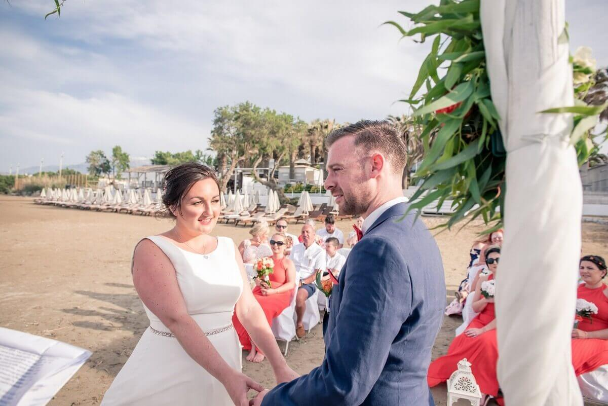 Bride and groom hold hands at Crete beach wedding