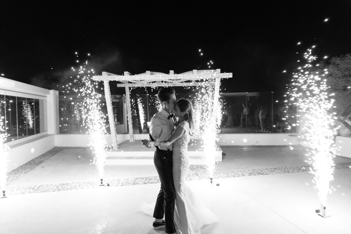 newly wed bride and groom dancing under fireworks in santorini